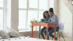 Two attractive curly haired mixed race young girls sitting at the table have fun while learning lessons and using tablet.  stock video footage