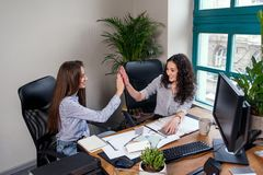 Two attractive female designers in blue shirts working together with new project on pc in the modern office. The girls stock photos