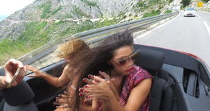 Two attractive female friends driving in convertible enjoying the wind. Slow motion of two attractive female friends driving in convertible car with top down and stock video