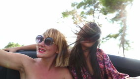 Two attractive female friends riding in windy back seat of convertible stock video footage