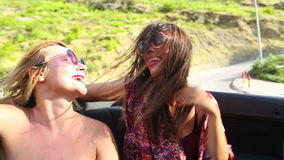 Two attractive female friends riding in windy back seat of convertible stock video