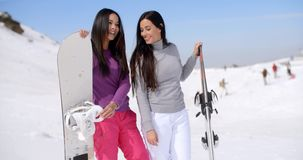 Two attractive female friends at a ski resort. Two attractive female friends at a winter ski resort standing holding their snowboards in a snowy landscape stock video