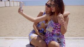 Two attractive female friends taking a selfie. Two attractive young female friends taking a selfie posing with their backs to the ocean and beach using a mobile stock video footage