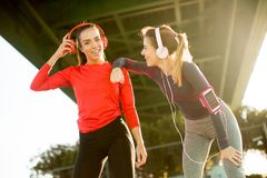 Two attractive female runner taking break after jogging outdoors Stock Photography