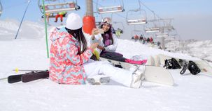 Two attractive female snowboarders. Sitting in the snow near a ski lift at a mountain resort surrounded by their gear stock video footage