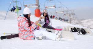 Two attractive female snowboarders. Sitting in the snow near a ski lift at a mountain resort surrounded by their gear stock footage
