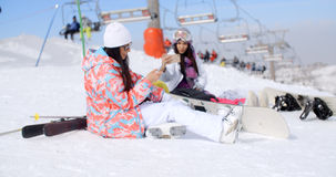 Two attractive female snowboarders Stock Photos