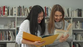 Two female students compare information in two books at the library stock images