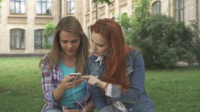Female students listen to music on smartphone on campus. Two attractive female students listening to music on smartphone on campus. Cute caucasian brown haired stock video footage