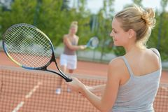 Two attractive female tennis players discussion at court. Two attractive female tennis players discussion at the court Royalty Free Stock Image