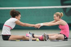Two attractive female tennis players stretching at court. Two attractive female tennis players stretching at the court Royalty Free Stock Image