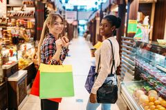 Two attractive females in food-court, shopping. Two attractive females in food-court after shopping. Shopaholics in sweets department, consumerism lifestyle royalty free stock images