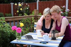 A happy same sex couple at home in the garden. Two attractive feminine middle aged gay women smiling together, embracing, looking happy, laughing at something on royalty free stock photography