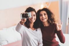 Two attractive friends making memorable photo. Memorable photo. Two attractive curly-haired friends feeling wonderful while making memorable photo together stock photography
