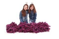 Two attractive girl sits with lilac. Royalty Free Stock Image