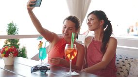 Two attractive girlfriends having fun and making selfie in restaurant on the seashore in summer weekend.