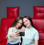 Two attractive girlfriends makes selfie on camera Stock Photography