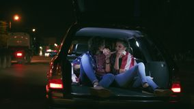 Two attractive girlfriends sitting in the open trunk of the car, talking and eating burgers during the night in the city. Slowmotion shot stock footage