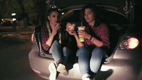Two attractive girlfriends sitting in the open trunk of the car, talking and eating sandwiches, drinking from the paper stock footage