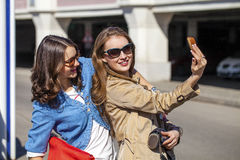 Two Attractive Girlfriends Taking Self Portrait with Their Phone Stock Images