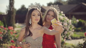 Two attractive girls in beautiful dresses and. Crowns laughing and doing phone selfie in garden with roses stock footage