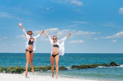 Two attractive girls in bikinis jumping on the beach. Best friends having fun stock photos