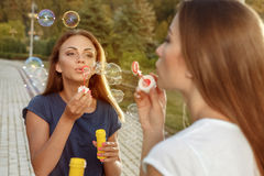 Two attractive girls blowing bubbles. In the park Royalty Free Stock Image