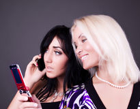 Two attractive girls calling by mobile. To friends Royalty Free Stock Photos