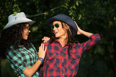 Two attractive girls in cowboy hats and sunglasses Stock Photos