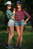 Two attractive girls in cowboy hats and sunglasses Royalty Free Stock Photos