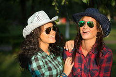 Two attractive girls in cowboy hats and sunglasses. Walking in the park Royalty Free Stock Images