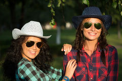 Two attractive girls in cowboy hats and sunglasses Stock Images