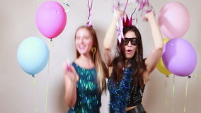 Two attractive girls dancing in photo booth. Two attractive girls dancing in party photo booth stock video footage