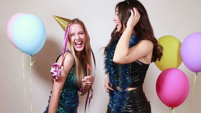 Two attractive girls dancing in photo booth stock video footage
