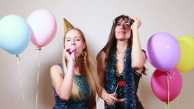 Two attractive girls dancing in photo booth stock footage
