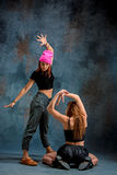 The two attractive girls dancing twerk in the studio. The two attractive girls dancing twerk iat the blue studio background stock photos