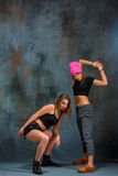 The two attractive girls dancing twerk in the studio. The two attractive girls dancing twerk iat the blue studio background stock images