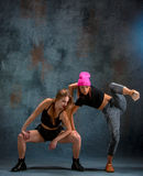 The two attractive girls dancing twerk in the studio. The two attractive girls dancing twerk iat the blue studio background royalty free stock image