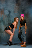 The two attractive girls dancing twerk in the studio. The two attractive girls dancing twerk iat the blue studio background royalty free stock images