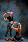 The two attractive girls dancing twerk in the studio. The two attractive girls dancing twerk iat the blue studio background royalty free stock photos