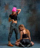 The two attractive girls dancing twerk in the studio. The two attractive girls dancing twerk iat the blue studio background stock photo