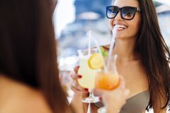 Two attractive girls drinking cocktails. On beach Stock Photography