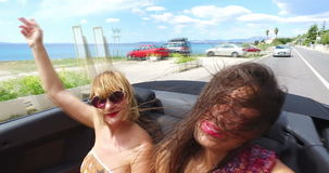 Two attractive girls driving in convertible with top down and enjoying the wind stock video