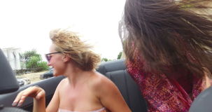 Two attractive girls driving in convertible with top down and enjoying the wind. Slow motion of two attractive girls driving in convertible car with top down and stock video