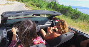 Two attractive girls driving in convertible with the top down stock video