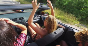 Two attractive girls driving in convertible with the top down stock footage