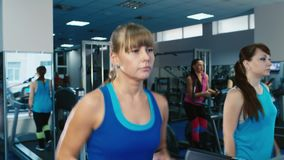 Two attractive girls exercise on a treadmill at the gym.  stock footage