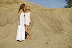 Two attractive girls friends. Blond and brunette over sand background Royalty Free Stock Photo
