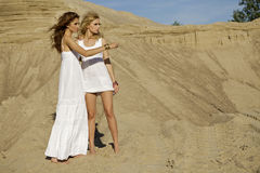 Two attractive girls friends. Blond and brunette over sand background Stock Photography