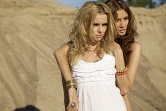 Two attractive girls friends. Blond and brunette over sand background Royalty Free Stock Photos